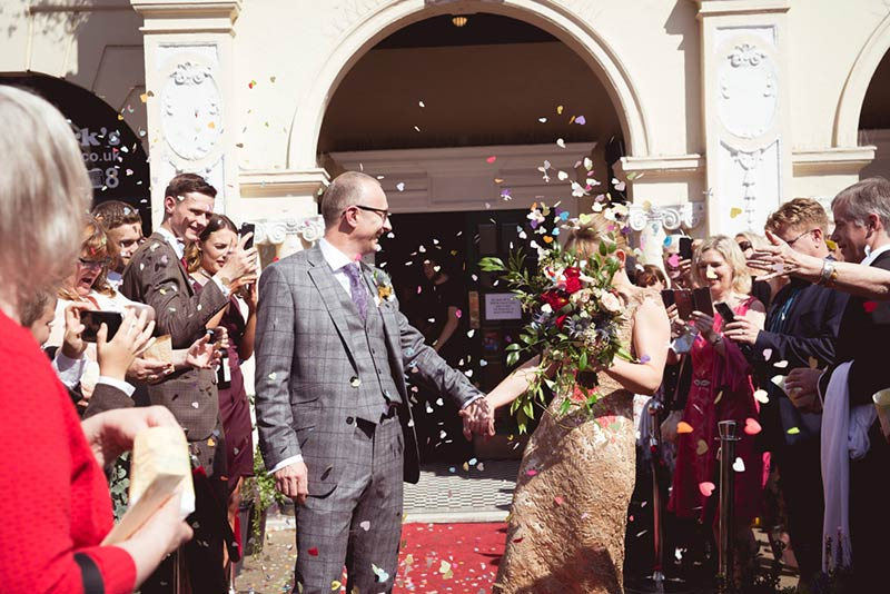 Newly married couple outside church with confetti